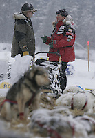 Paul Gebhart talks with race judge Al Marple at the Nikolai checkpoint on Tuesday afternoon shortly after checking in.  Gebhart lost his entire team in the Farewell Burn after his gangline broke.  Doug Swingley gave him a ride to where some buffalo hunters on snowmachine gave him a ride further to put his sled and team back together.