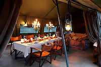 Heavy velvet draperies hang on the canvas dining tent lending it a cosy and intimate space for bush meals at a boutique style guesthouse. The interior has a rustic feel, with the talents of regional artists adding many of the finishing touches, for example the wrought iron candelabra and glass-beaded candleholders on the table are made by Masai women.