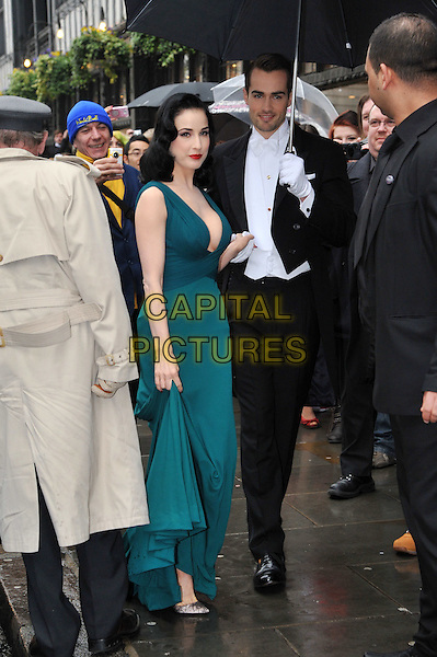 Dita Von Teese .Dita Von Teese, the burlesque superstar, appeared at Liberty London to launch her debut fragrance, named after herself, London, England..May 1st, 2012.perfume full length dress low cut neckline cleavage red lipstick teal blue green holding hands umbrella black suit white shirt gloves .CAP/BF.©Bob Fidgeon/Capital Pictures.