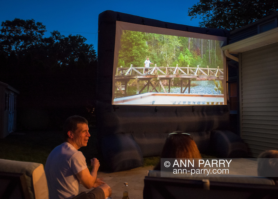 """Merrick, New York, USA. 11th June 2017.  """"American Grit"""" TV show contestant CHRIS EDOM (bottom left), 48, of Merrick, hosts Viewing Party for Season 2 premiere.  Edom family's friends and neighbors watched Episode 1 of the Fox network TV show on large screen in their backyard. Edom was the last contestant picked for a team."""