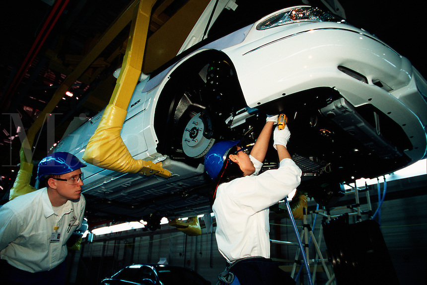 An American supervises a Chinese worker at a General Motors Buick assembly line. Shanghai, China.