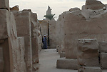 A guide beckons from amongst the masonry.Part of the ninth pylon is in the background.Karnak is part of the ancient city of Thebes ( built in and around modern day Luxor).The building of the Temple complex at Karnak began in the reign of the Pharaoh Senusret I who ruled Egypt from 1971-1926 BC. Approximately 30 Pharaohs contributed to the building of the complex and in so doing made it the largest ancient religious site in the world. The ancient name for Karnak was Ipet-isut (Most select of places).
