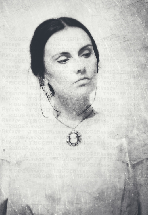a black-white portrait of young woman wearing victorian blosue with camea necklace with proud sight