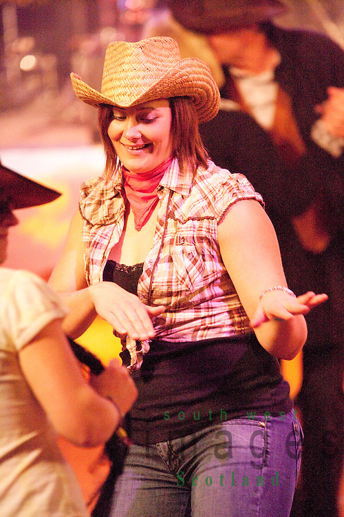 Creetown Country Music Festival young girl dancing on dance floor in cowboy hat and jeans. Dumfries and Galloway Scotland UK