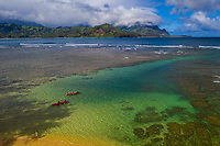 Kayakers head out between reefs, with Mount Makana or Bali Hai in the distance, Princeville, Kaua'i.