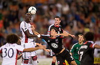 Saer Sene (39) of the New England Revolution heads the ball out of the box and away from Dejan Jakovic (5) of D.C. United during a Major League Soccer game at RFK Stadium in Washington, DC.  New England defeated D.C. United, 2-1.