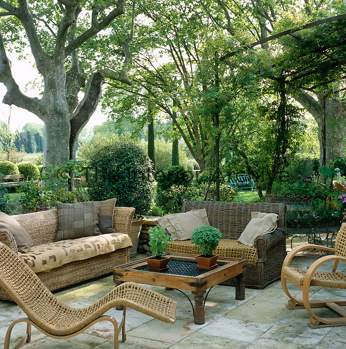A combination of cane furniture grouped around a simple table on a stone-flagged terrace in this shady garden