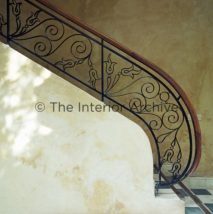The railing on the staircase features ornate floral-patterned metalwork with a curved wooden banister