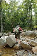 A hiker crosses a section of the Swift River on Sawyer River Trail during the summer months. Located in the White Mountains, New Hampshire USA