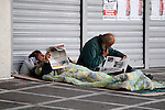 Homeless men are reading newspaper outside a closed bank during a demonstration in central Athens. People who work at the public sector demonstrate against IMF and the austerity measures.
