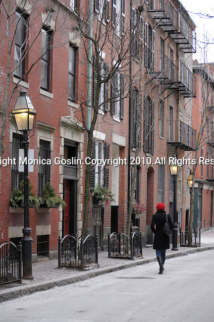 A street in Beacon Hill in Boston, MA. A girl with a red hat walks down a street in Beacon Hill in Boston, MA.