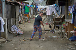 A woman sweeps the street in front of her home in Pulilan, a village in Bulacan, Philippines, where the Kapatiran-Kaunlaran Foundation (KKFI) operates a preschool. <br /> <br /> KKFI is supported by United Methodist Women.