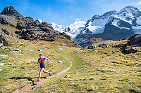 A woman trail running through a green meadow above Zermatt, Switzerland with the Breithorn in the background.