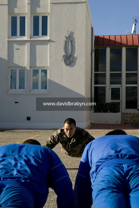 Fresh volunteers to join the French Foreign Legion wearing the traditional light blue suit perform push-ups as demonstrated by an instructor at the force's headquarters in Aubagne, France, 10 December 2007.