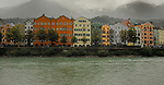 Pastel colour buildings overlooking river Inn, with background of mountain and clouds. Innsbruck, Tyrol, Austria.
