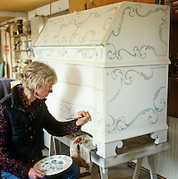 A woman painting an intricate pattern on a wooden desk