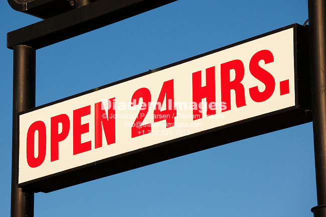 Service station sign that reads open 24 hours.