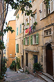 FRANCE, Villefranche sur Mer, a street with yellow buildings and green shutters. Laundry is hung outdoors