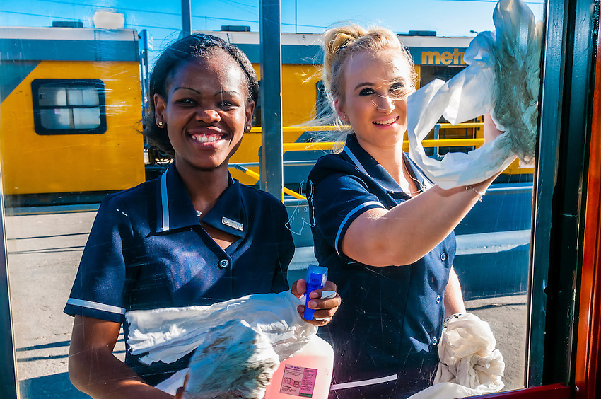 Train hostesses Zodwa Ndlovu and Sasha De Lange cleaning windows during a brief stop aboard the luxury Rovos Rail train from Pretoria to Cape Town, South Africa.