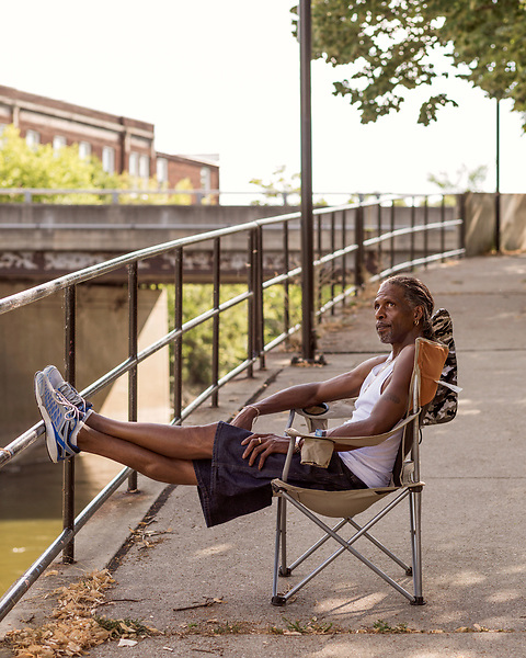 August 5, 2016. Flint, Michigan.<br />  DeAidre Avant, a truck driver and lifelong Flint resident, watches his fishing pole along the downtown section of the Flint River. Avant pulled several cat fish from the river and said he had been fishing it for years. <br />  In April 2014, the city of Flint switched its water source from the Detroit Water and Sewerage Department to using the Flint River in an effort to save money. When the switch occurred, the city failed to have corrosion control treatment in place for the new water. This brought about a leaching of lead from pipes into the water, increasing the lead content in the drinking water to levels far above legal limits. After independent sources brought this to light, the city admitted the water was unsafe and legal battles have ensued between resident and the local and state governments.