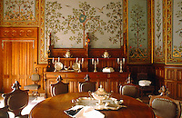 The walls of the dining room are covered in wood panelling and frescos of trees