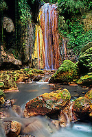 731400020 A peaceful grotto setting frames diamond falls with moss covered boulders in the foreground on a private estate on the caribbean island of saint lucia