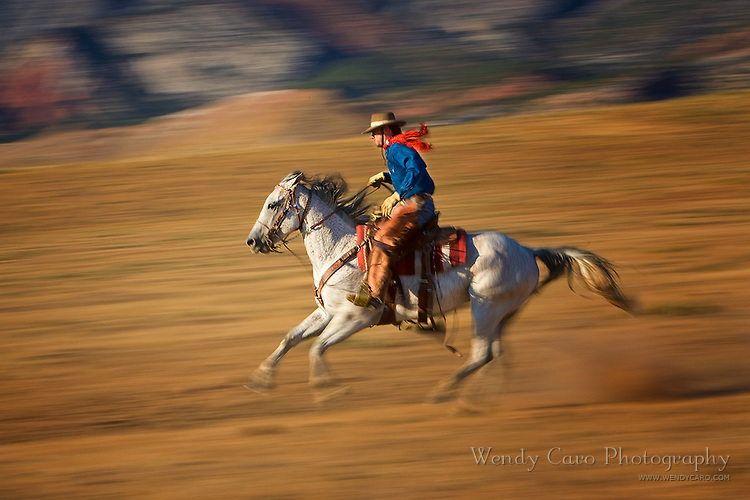 Cowboy with red scarf galloping across the plain, slow motion, pan blur, Big Horn Mountains, Wyoming.