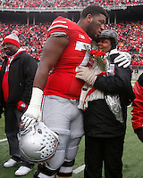 Ohio State Buckeyes offensive linesman Marcus Hall (79) embraces family as nineteen seniors were recognized before Saturday's NCAA Division I football game against Indiana at Ohio Stadium in Columbus on November 23, 2013. (Barbara J. Perenic/The Columbus Dispatch)