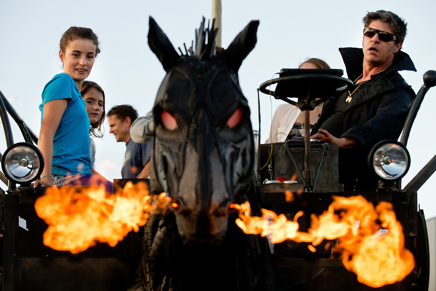 "Leilani Wirth-Martin, 12, left, and Jaia Aginsky, 9, watch flames shoot from the ""Chester"" the fire-breathing horse art car operated by Jason Anderholm, right, during the Barlow Street Fair in Sebastopol, Calif., on November 2, 2013. (Alvin Jornada / The Press Democrat)"
