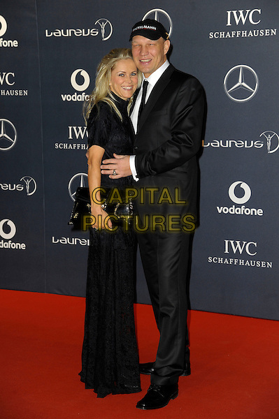 Axel Schulz and Frau Patrizia.Arrivals at the Laureus 2012 World Sports Awards held at the Queen Elizabeth II Centre, London, England..February 6th, 2012.full length black suit dress clutch bag baseball cap hat arms around waist .CAP/CAS.©Bob Cass/Capital Pictures.