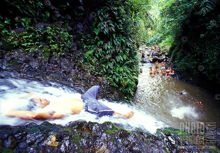 Man lying in stream of  jungle waterfall, Maunawili Trail, Kailua, Oahu. Hawaii
