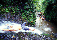 Man lying in stream of  jungle waterfall, Maunawili Trail, Kailua, Oahu. Hawaii