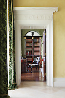 An ornate plasterwork doorway leads through to the library from the entrance hall which has windows draped with silk velvet curtains