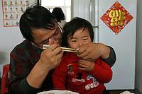 Li Fang (gauche) aide sa petite-fille Li Siqi (droite) à manger, pendant le déjeuner, à Baoshan, près de Shanghai, le 7 mai 2008. Photo par Lucas Schifres/Pictobank