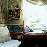 In the guest bedroom of a house in Jamaica a cabinet of curiosities has been against a wall where accumulated layers of paper and paint have been scraped away to create an original and unique decorative surface