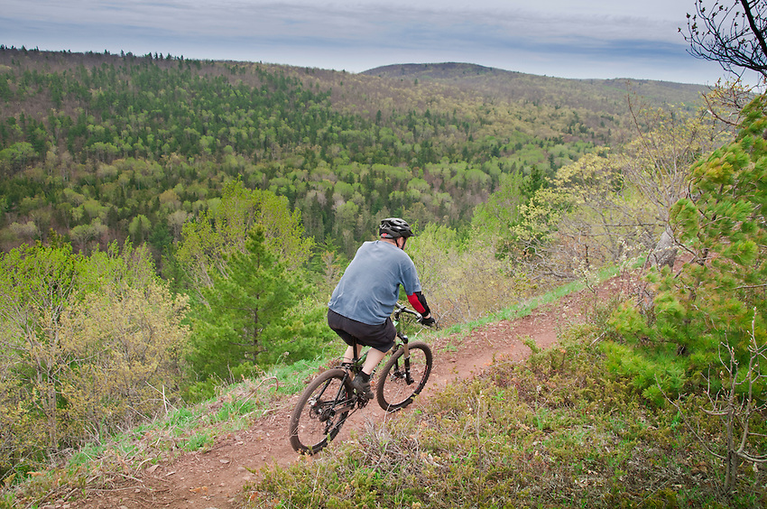 A male mountain biker rides the Woopidy Woo single track trail along Brockway Mountain in Copper Harbor Michigan.