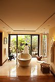 MAURITIUS, Flic en Flac, Wolmar, a guest waits for the tub to fill in her luxury villa at the Maradiva Villas Resort and Spa