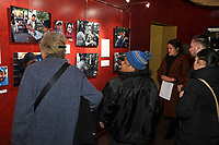 (180314RREI7976) About 200 people attended the opening of La Esquina - The Corner exhibition at Gala Theatre. The documentary project La Esquina revolves around the history of the Latinos at the corner of Mt. Pleasant St. and Kenyon St. NW. Maribel, one of the esquineros looks at the exhibition. Washington DC March 14, 2018 . ©  Rick Reinhard  2018     email   rick@rickreinhard.com