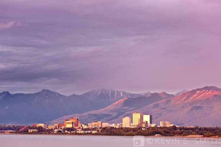 Sunset light illuminates the downtown Anchorage Skyline overlooking Knik Arm during a thunderstorm, Spring, Southcentral Alaska, USA.