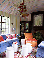 """In the colourful hand-painted library, the Bilhuber-designed wing chair is upholstered in Villa Romo cotton with a cushion of Malabar velvet, the milk glass stools are from Anthony Dodd Home, and the crystal-and-wood """"dragon boat"""" is antique"""