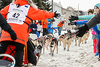 Kristin Bacon runs down Cordova Street giving high-fives during the Ceremonial Start of the 2016 Iditarod in Anchorage, Alaska.  March 05, 2016
