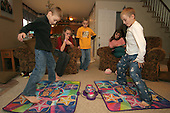 """Joseph Salem 8 (left) of Telford, Pa., competes with his older brother Sam 12 at """"Dance Maker Star Lite"""" as Selene 12, Jake (Sam's twin brother) and Julianne (Selene's twin sister) keep score on a cold Thursday March 2, 2006. The American flag hangs in the boys bedroom. While still in the orphanage at 10 months, Sophia would wrestle a bottle of milk away from other babies and give it to her brother Joseph. That act saved her brother's life. Lisa and Hythem Salem adopted Sophia and Joseph from Russian at the age of 11 months. 20 months ago, Lisa and Hythem adopted Selene and twin sister Julianne, Sam twin to Jake, the younger children's biolgical siblings. photo by jane therese"""