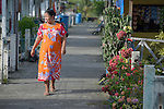 A woman walks along a sidewalk in Kuala Bubon, in Indonesia's Aceh province. The community of 118 houses was built by the ACT Alliance after the village's tsunami survivors refused to accept government plans to relocate them inland far from the sea. After the houses were built, the community then successfully fought a government plan to demolish part of the new village to make way for a new highway.