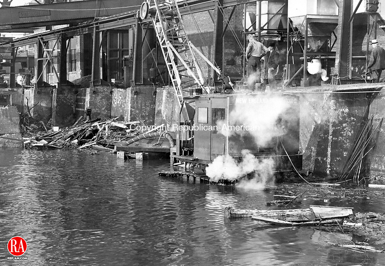 Water recedes at the American Brass Co. coal pit yesterday and workmen started to steam clean the crane, the cab of which was covered almost to the top by flood waters Saturday. Two pumps and a compressor are in the water behind the South End power plant. 18 October 1955.