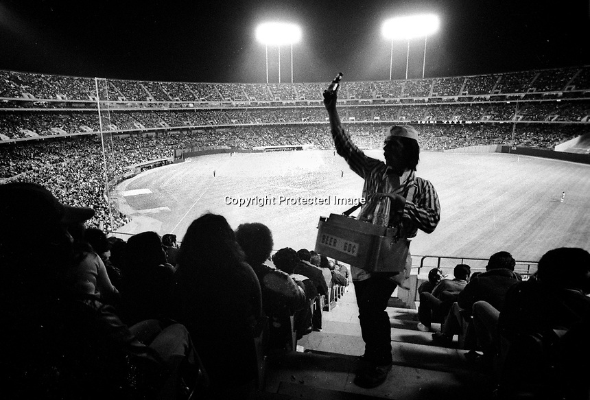 CROWD at the Oakland Alameda County Coliseum of 41,000 for Monday nite game Oakland Athletics against the Detroit Tigers. Aug 20,1973..(note beer vendor beer 60c) (photo/Ron Riesterer)