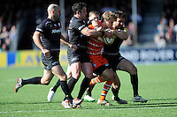 Mathew Tait of Leicester Tigers is tackled by Brad Barritt and Marcelo Bosch of Saracens during the Aviva Premiership Rugby match between Saracens and Leicester Tigers at Allianz Park on Saturday 11th April 2015 (Photo by Rob Munro)