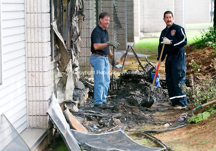 WATERBURY, CT. 11 SEPTEMBER 2008-091108SV01--Fire Investigators Terry Ballou and Dan Aybar dig through the rubble of an apartment fire at 2221 East Main Street in Waterbury Thursday. Steven Valenti Republican-American