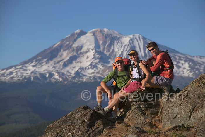 A  photo of three friends taking a break on the summit of a mountain near Mount Adams, WA.