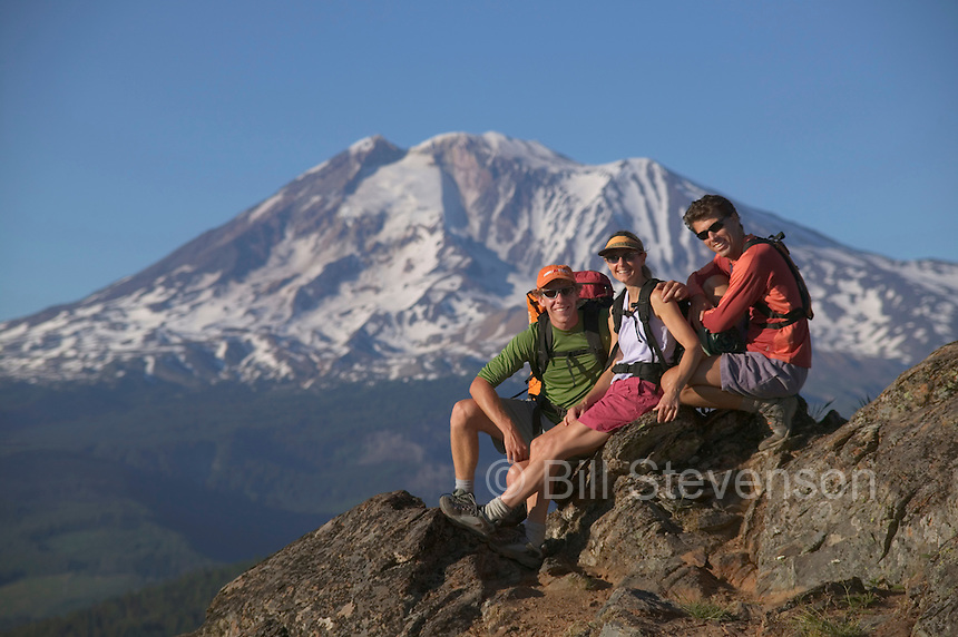 A  photo of three friends taking a break on the summit of a mountain near Mount Adams, WA.