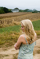 Blonde woman in blue-green dress standing in front of field